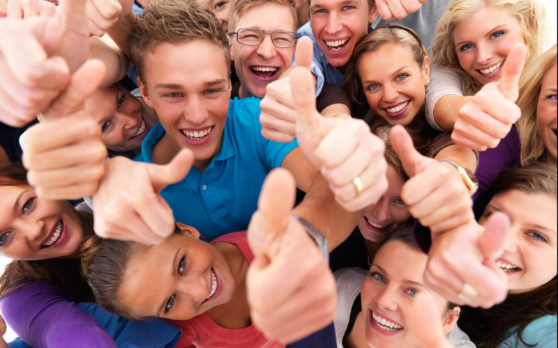 Top view portrait of men and women standing together and showing thumbsup sign